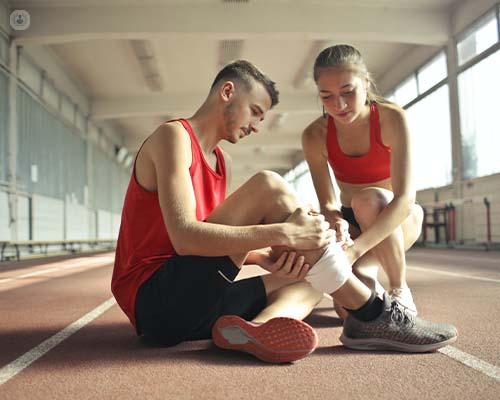 Woman helping sportsman with leg injury during cardio training