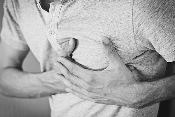 Man holds chest as he struggles with indigestion.