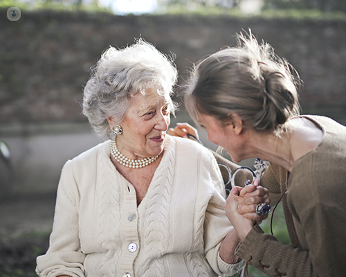 An elderly woman and younger woman sitting together and holding hands.