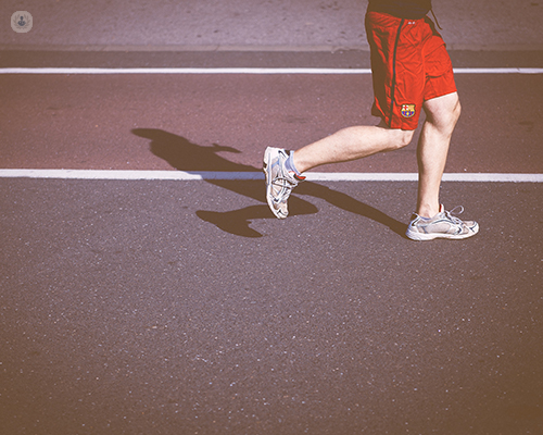 Man running on track. Knees are bent.