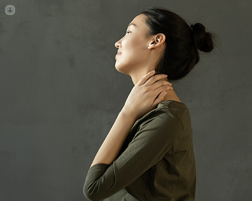 Woman with hand on neck and thoracic area.
