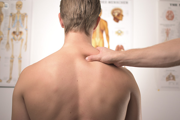 Doctor checks and massages patient with back pain